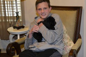 Boy Holding Black Puppy